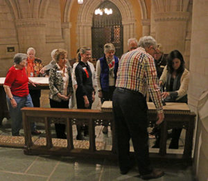 small crowd standing around a needlework demonstration