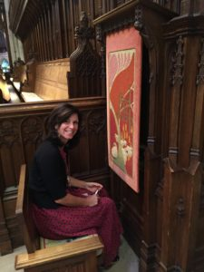needlework artisan sitting and smiling in a church