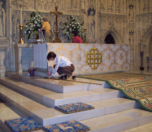 woman kneeling to measure alter rug on the floor