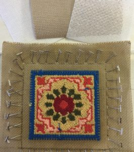 needlepoint pins stuck in floral needlework canvas
