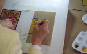 a woman painting on needlepoint canvas